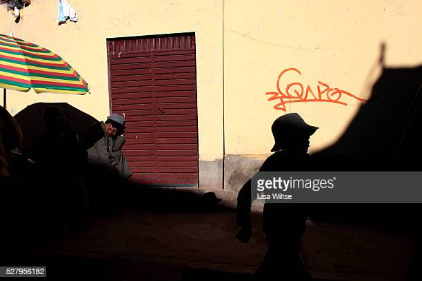 Virgen del la Candelaria. A young boy walks past a man passed out from drinking during the Fiesta de la Virgen de la Candelaria is held to honour the...