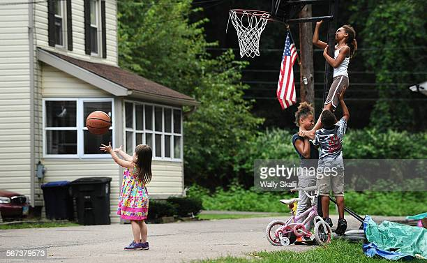 Children teamup to adjust the the basketball rim as the former childhood home of LeBron James sits in the background on Overlook Place in Akron Ohio