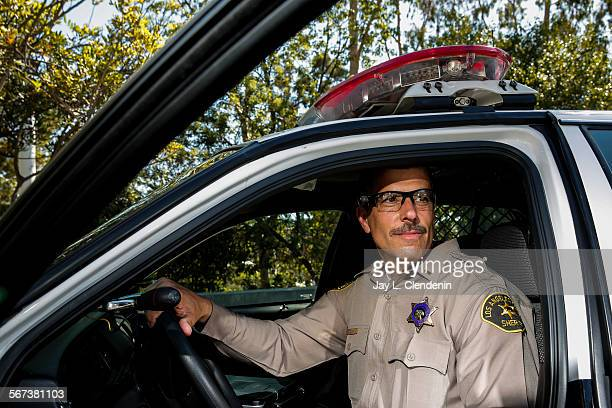 PARK CA SEPTEMBER 17 2014County of Los Angeles Sheriff's Lt Chris Marks poses in a patrol car wearing the Taser Axon Flex onofficer camera system...
