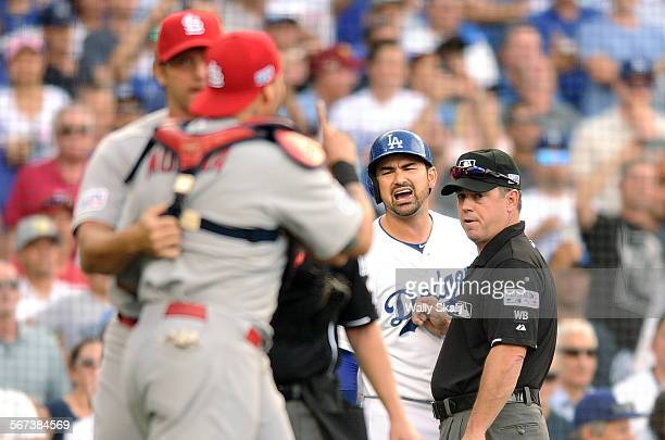 Dodgers Adrian Gonzalez is held by as he argues with Cardinals catcher Yadier Molina in the 3rd inning in Game 1 of the NLDS in Los Angeles Friday