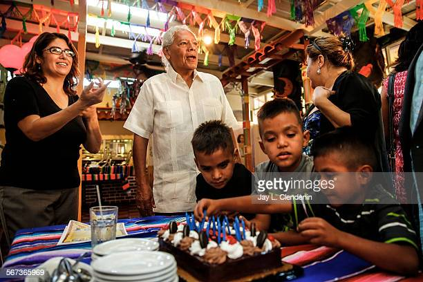 LOS ANGELES CA SEPTEMBER 23 2014Father Richard Estrada center gathers people including brothers Jefferson left Andersen7 and Anthony Yanes to...