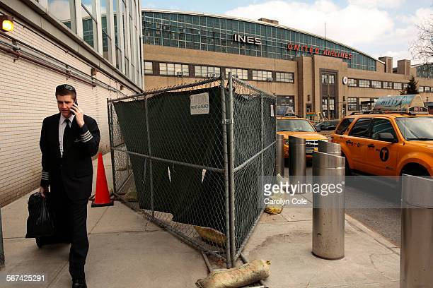 La Guardia Airport has been ranked America's worst several times. An airline employee walks past sand bags and construction between B and C terminals...