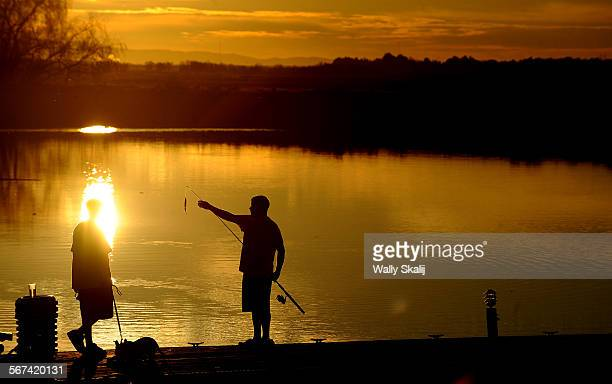 Two young men fish from the dock at the Tower Park Resort & Marina in the California Delta near Stockton, California.