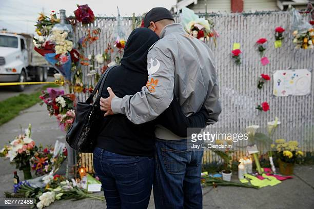 Mourners hug next to flowers near the site of the warehouse fire in Oakland CA December 4 2016 A fire broke out during a party Friday night at a...