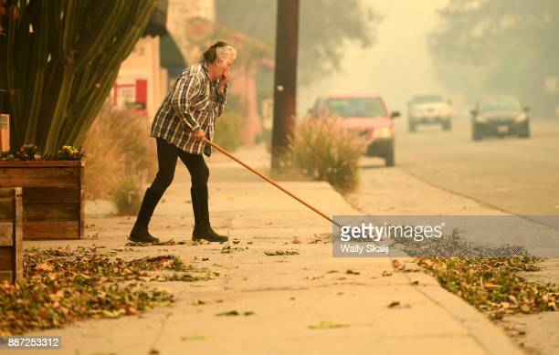 Buisness owner Violet Chohen sweeps leaves away from her store along Highway 150 in Oja iCalifornia on December 6 2017