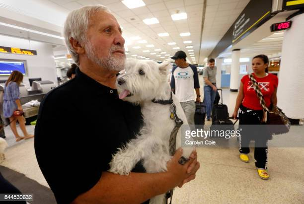 Ron Rosen, age 68, holds his dog Max, while they wait for a flight out of Miami on Friday, Sept. 8, 2017. He and his wife and pregnant daughter are...