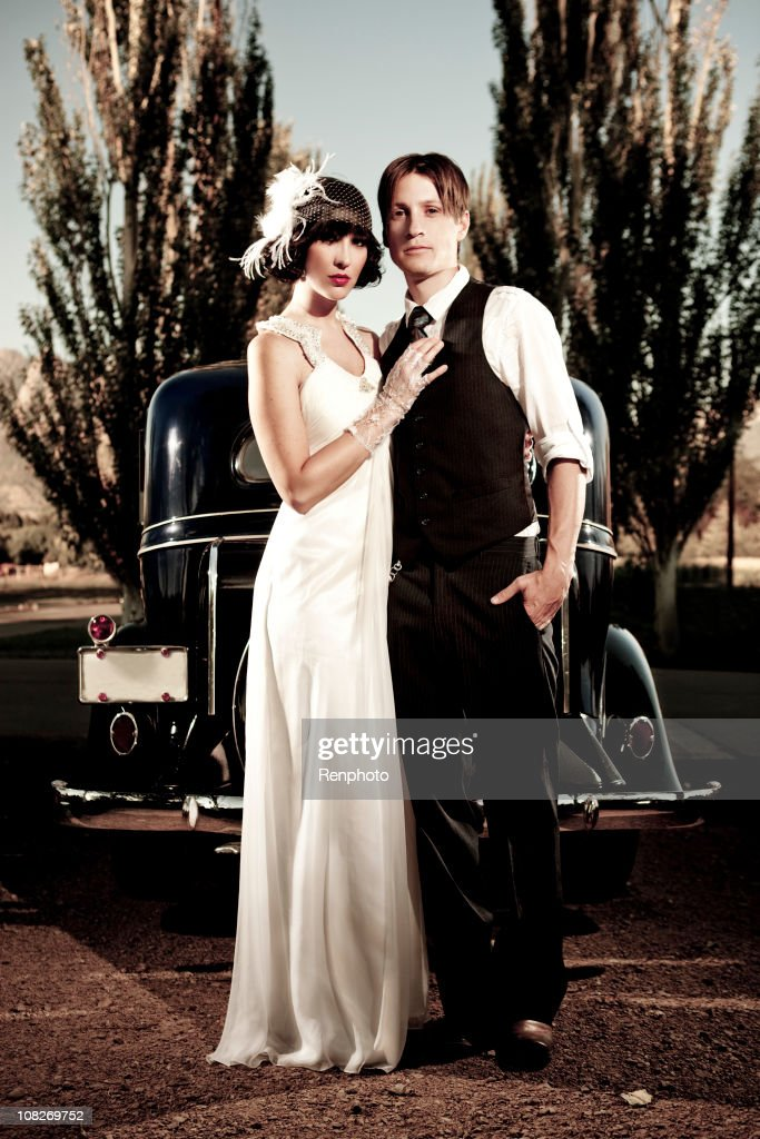 20s style couple standing in front of vintage car : Stock Photo
