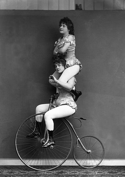 Victorian trick cyclists performing a balancing act....