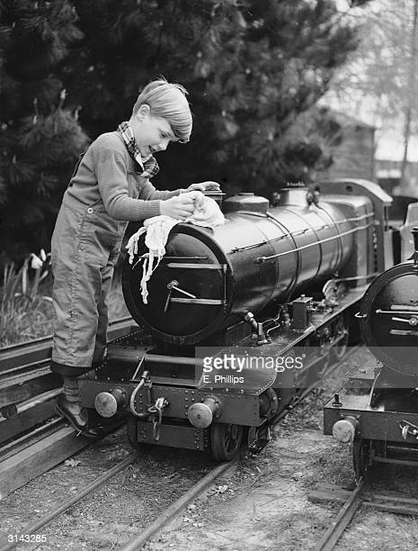The grandson of model railway enthusiast J A Holder helps clean one of the trains at his miniature railway in Bucklers Hard near Beaulieu