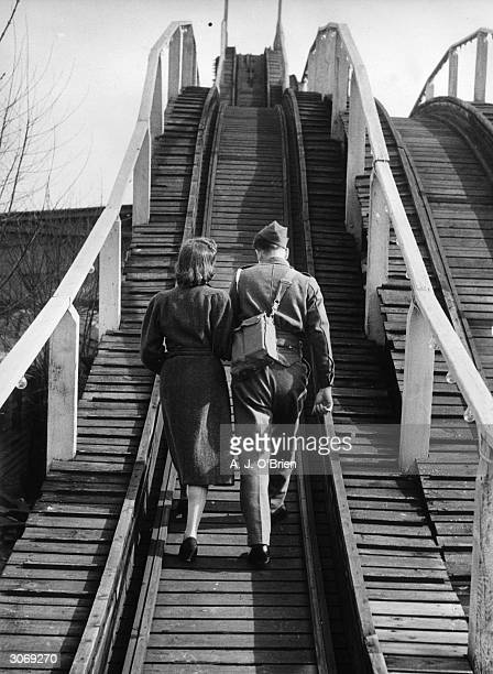 A soldier on leave from World War II takes a walk with his girlfriend along the tracks of the rollercoaster at Dreamland an amusement park being...