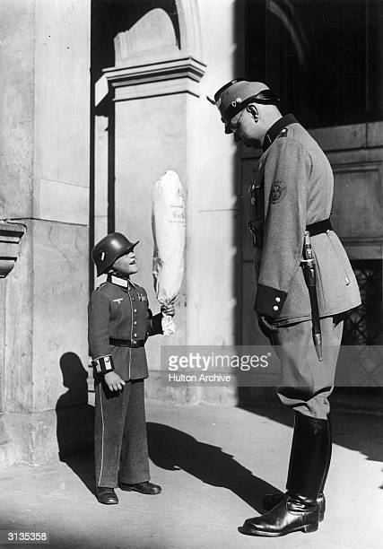 The smallest German soldier wants to deliver a bunch of flowers to his 'dear' fuehrer by hand.