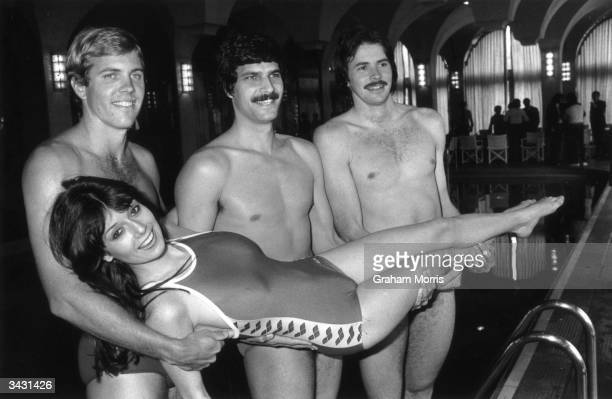 Swimmers l to r Gary Hall Mark Spitz and David Wilkie who are all Olympic medallists prepare to throw Laraine Humphrys into the pool
