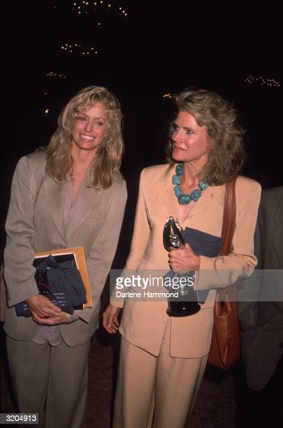 American actors Farrah Fawcett and Candice Bergen smile while standing together Bergen holds the Emmy Award that she won for Outstanding Lead Actress...