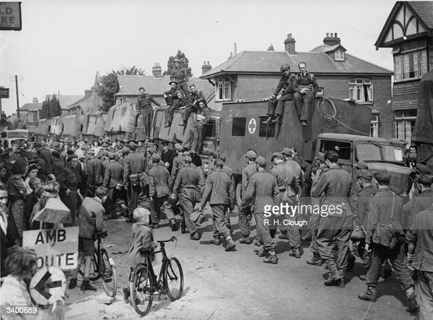 Local residents and British soldiers waiting to embark for Europe watch as a seemingly endless stream of newly captured German prisoners of war are...