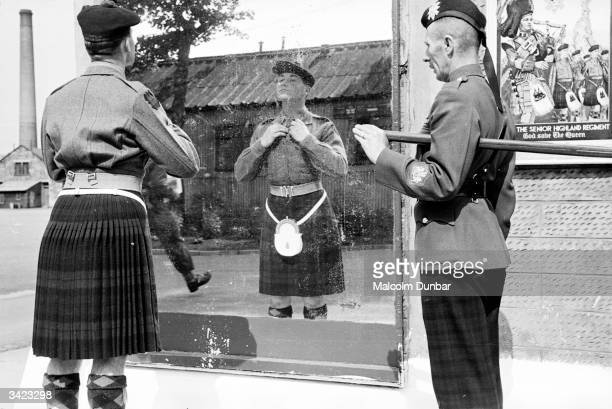 Private Grainger of the Black Watch checks his uniform in the primping mirror at the Black Watch Depot, Queen's Barracks, Perth, watched by...