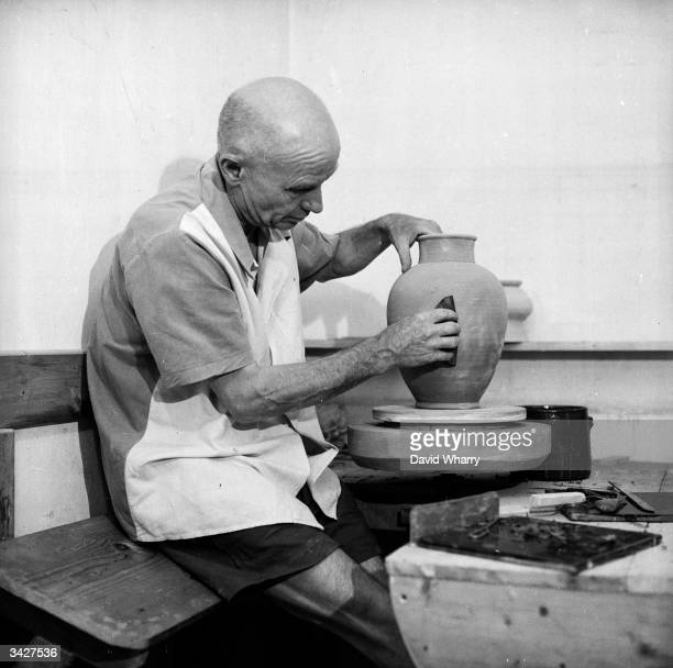 Ceramicist Claude Renoir son of Impressionist painter Pierre Auguste Renoir smooths the sides of a Grecianstyle urn on a potter's wheel in Les...