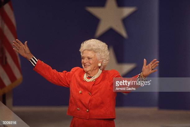 First Lady Barbara Bush, wearing a red outfit, opens her arms wide onstage at the Republican Convention.