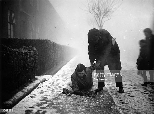 A man stoops to help an unwary pedestrian who has slipped on an icy pavement in Walthamstow East London