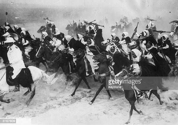 Libyan cavalrymen charging across the sand on horseback during a military display