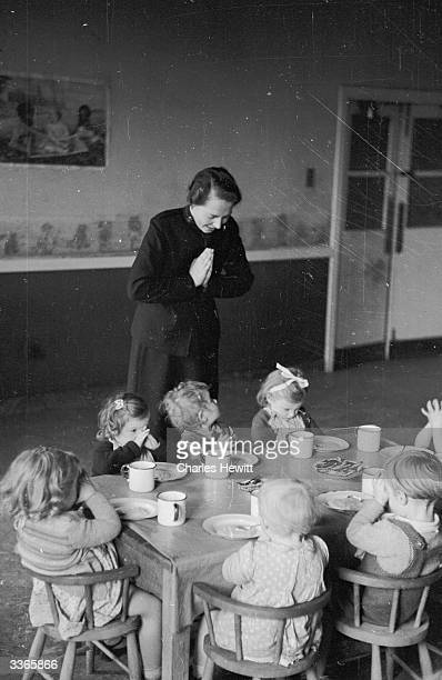 A Salvation Army member and small children say grace before a meal Original Publication Picture Post 4485 Salvation Army Miss Ross Goes To War pub...