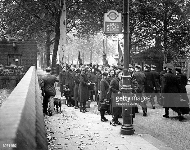 The avenue is full of trees the streets are full of leaves and soldiers of the Salvation Army wait at the bus stop on their way to war Original...