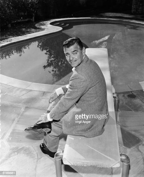 American leading man Clark Gable sitting by the swimming pool at his home