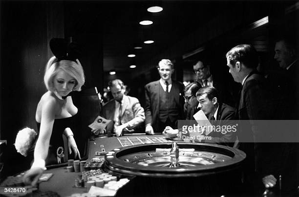 A bunny girl croupier at the Playboy club supervises a roulette wheel