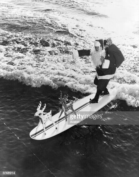Father Christmas arrives at Cypress Gardens Florida on his surfboard