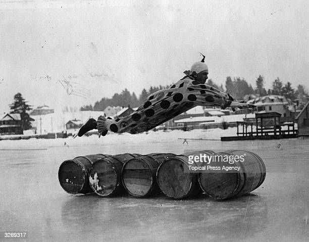 Ice skater Ernest Lamy dressed as a clown entertaining crowds at Saranac Lake New York by diving over 5 barrels during the International Speed...