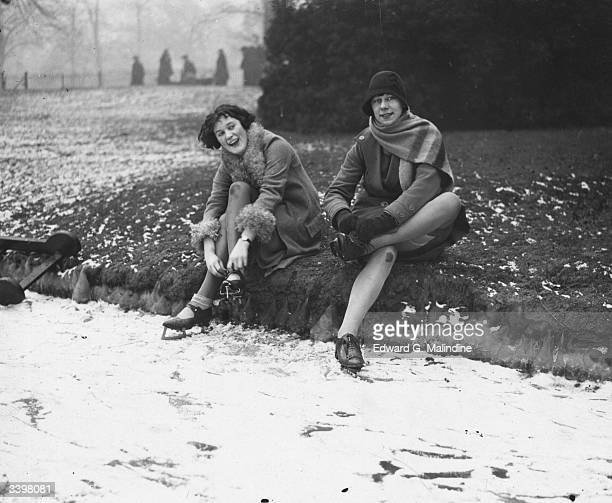 Two women adjusting their ice skates on the Sepentine in London's Hyde Park.