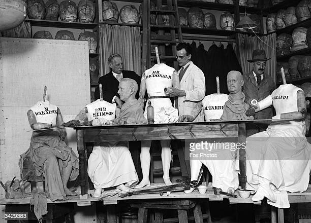 Craftsmen at the Madame Tussaud's workshop arrange headless wax figures of Wakatsuki, Stimson, MacDonald, Tardieu and Grandi into a tableau of a...