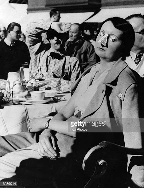 A young woman protects her eyes and nose from the sun while dozing at a roadside cafe on the French Riviera by covering them with silver paper
