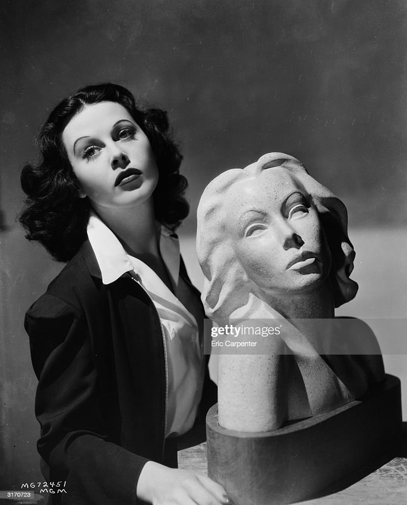 Austrian born actress Hedy Lamarr (1913 - 2000) poses with a bust of herself.