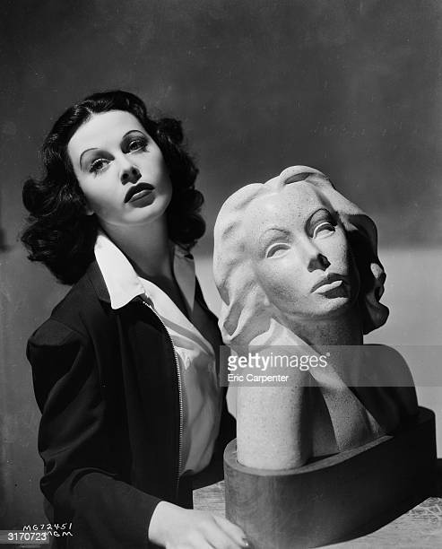 Austrian born actress Hedy Lamarr poses with a bust of herself.