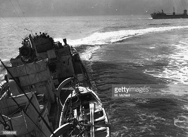 British destroyer sweeps round a convoy of ships which it is protecting in the Atlantic.