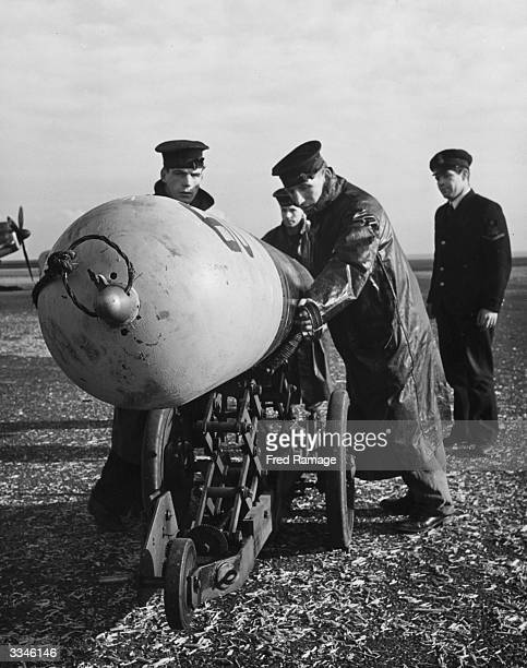 A torpedo is brought up to be loaded beneath a plane at a Fleet Air Arm Station