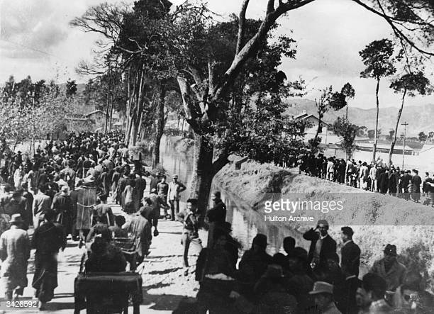 Chinese citizens making their way along the bank of a canal to reach safety in the hills away from the attacking Japanese planes.