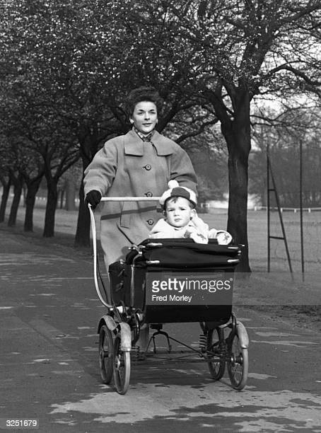 Woman takes her 2-year-old son for a walk in his pram in the park, north London.