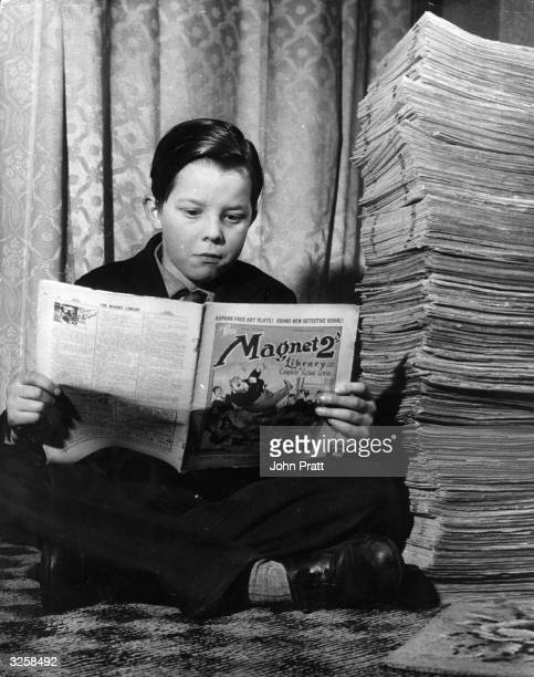 13 year old Michael Harris reads one of the 5000 schoolboy books and magazines in the collection amassed by his neighbour 57 year old Civil Servant...