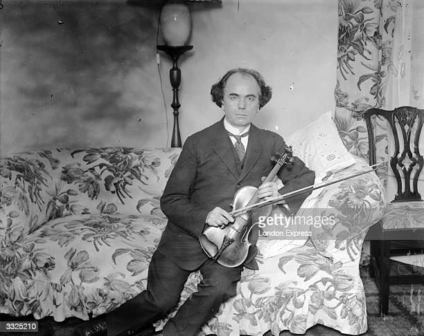 Czechborn violinist and composer Jan Kubelik sitting on a sofa in London holding his Strad violin