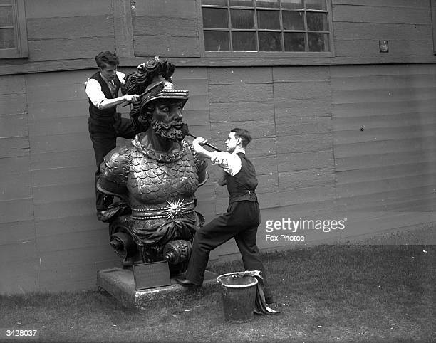 Dockers clean a figurehead from a ship's prow at Chatham Dockyard in Kent