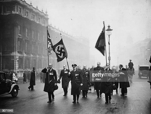 Bearing a swastika flag German exservicemen marching to the Cenotaph in London to lay a wreath They are guests of British exservicemen