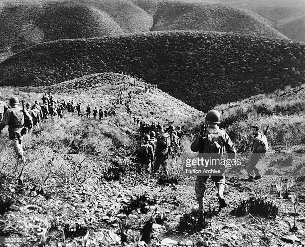 Rear view of U.S. Ranger battalion marching over hilly terrain in North Africa.