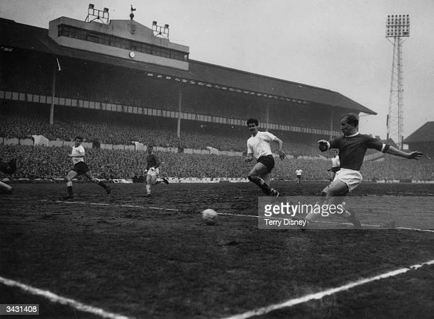 Manchester United footballer Bobby Charlton scores his team's first goal during a game against Tottenham Hotspur at Whitehart Lane London while the...
