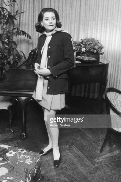 Full-length portrait of American broadcast journalist Barbara Walters, wearing a miniskirt, leaning against a piano in her home at 171 West 57th...