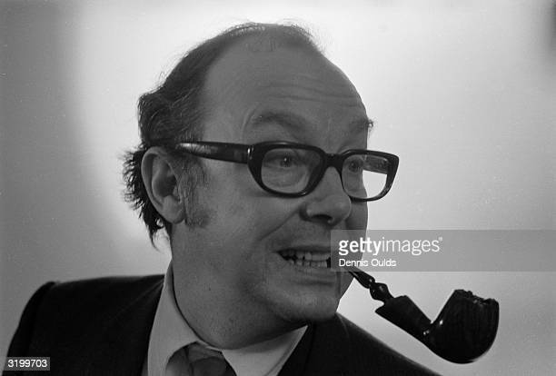 English comedian Eric Morecambe puffing away on his pipe at the Savoy Hotel London after winning the title of 'Pipeman of the Year' in the contest...