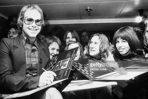 Pop star Elton John at Noel Edmonds record shop in the King's Road, Chelsea signing copies of his album, 'Don't Shoot Me I'm Only the Piano Player'.
