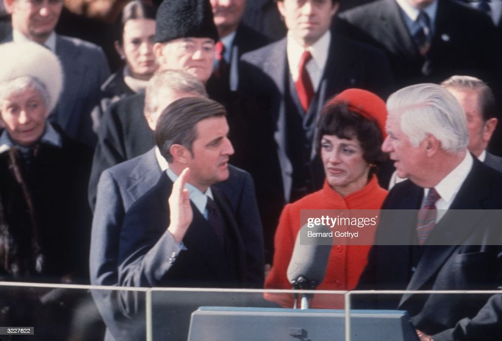 American Democratic politician Walter Mondale holds up his right hand and speaks, while being sworn in as U.S. vice president under President Jimmy Carter, as his wife, Joan, looks on, Washington, DC.