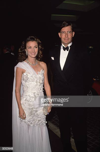 Britishborn actor Jane Seymour and her third husband David Flynn smile while attending a formal event Seymour wears a white strapless dress with...