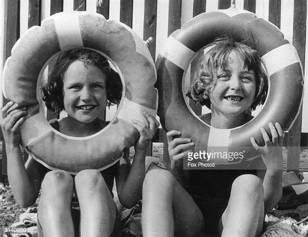 Two young girls smile through rubber rings on Brighton Beach